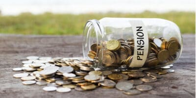 """Jar labelled """"pension"""" tipped over with coins spilling out"""